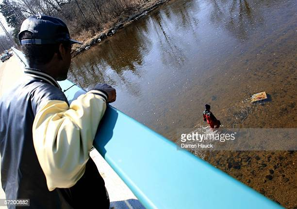 An unidentified man watches as a member of the Milwaukee police department dive team wades through water along the banks of the Milwaukee River in...