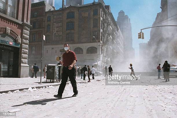 An unidentified man with a face mask walks on an ash covered street near Ground Zero after the collapse of the Twin Towers September 11, 2001 in New...