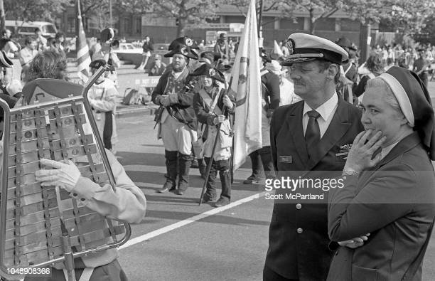 An unidentified member of the US armed forces stands beside a nun as they watch marching bands pass by during the Brooklyn Bridge's 100th birthday...