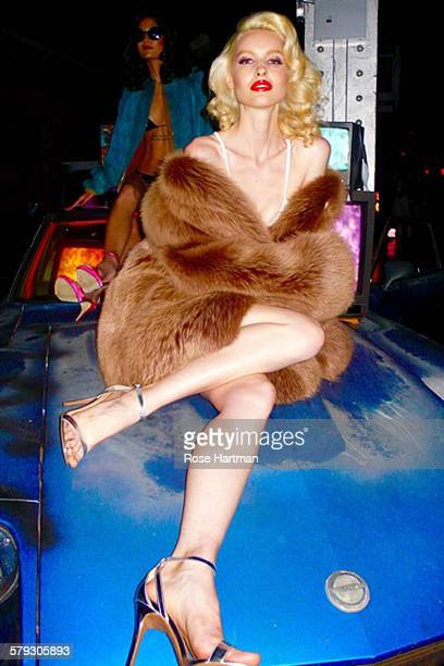An unidentified model dressed in a fur coat poses on the hood of a car at the launch party for the book 'Gloss The Work of Chris von Wangenheim' at...