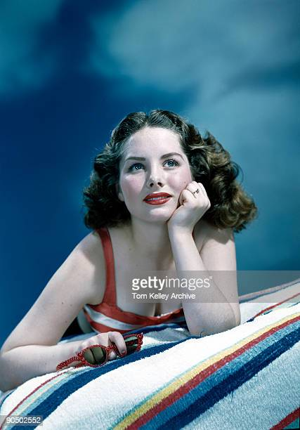 An unidentified model lies on a striped towel a pair of red sunglasses in one hand and gazes wistfully into the cloudy 'sky' of a photo studio 1950