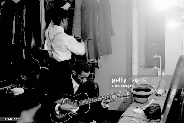 An unidentified musician plays guitar, while behind him, another man shorts through clothes on a rack backstage at the Apollo Theater, New York, New...