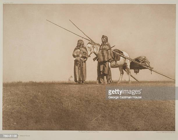 An unidentified Native American couple from the Blackfoot nation stand on a grassy rise with their dog and horse which is harnessed to a travois1926