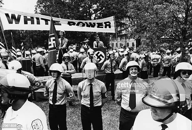 An unidentified neoNazi gives a speech from a podium under a 'White Power' banner in Lafayette Park surrounded by his followers who are in turn...