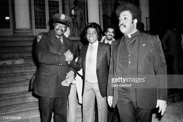 An unidentified New York City police officer shakes hands with American Soul and RB singer James Brown while religious and Civil Rights activist...