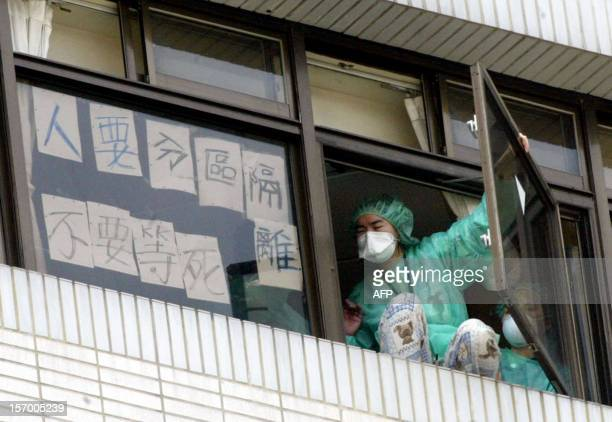 An unidentified nurse of Hoping Municipal Hospital attemps to jump from the hospital building in Taipei, 27 April 2003. Taiwan announced 27 April a...