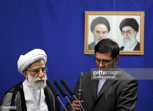 An unidentified offical puts a gun in place as the head of Iran's electoral body the Guardians Council Ahmad Jannati prepares to speak at the weekly...
