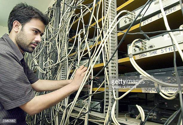 An unidentified Pakistani cable televison operator unplugs a cable channel connection following a ban on Indian channels imposed by the Pakistani...