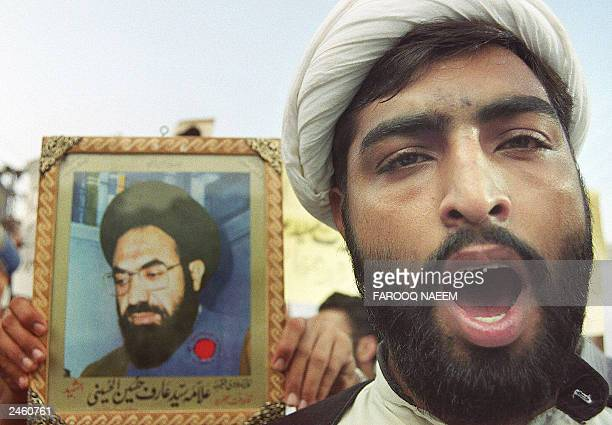 An unidentified Pakistani Shiite Muslim holds a picture of Pakistani Shiite leader the late Allama Syed Arif Hussain alHussaini while shouting antiUS...