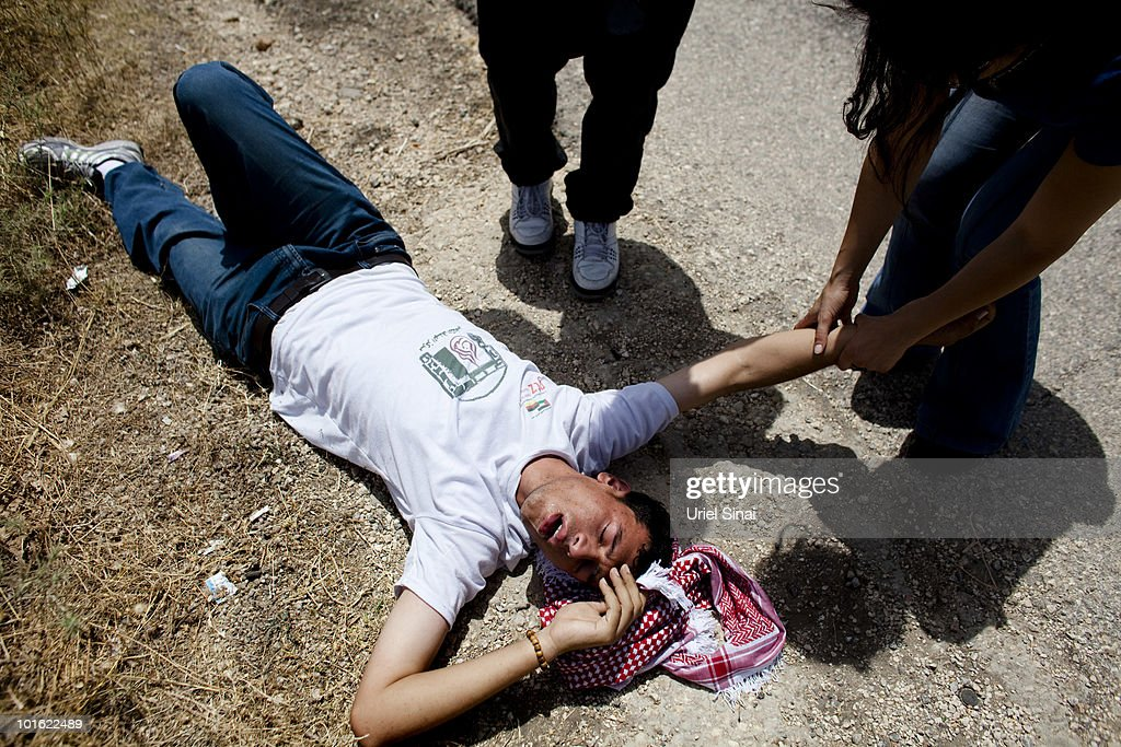 An unidentified Palestinian man lies on the ground after he inhaled tear gas near an Israeli barrier, against Israel's attack on a Gaza aid flotilla earlier this week, on June 4, 2010 in Bil'lan, the West Bank. Israel has faced international criticism over the deadly raid on May 31, aboard a ship carrying humanitarian aid to the Gaza Strip.