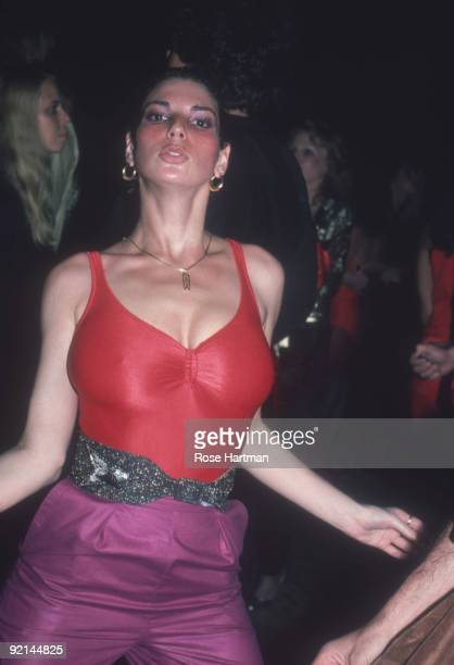 An unidentified partygoer in a red spandex tank top bejeweled belt and purple pants dances at the nightclub Studio 54 New York New York late 1970s or...