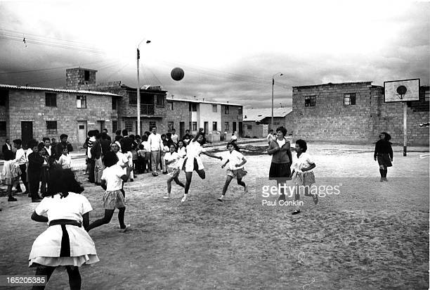 An unidentified Peace Corps worker oversees a game of basketball between female students at Ciudad Kennedy Bogota Colombia mid 1960s