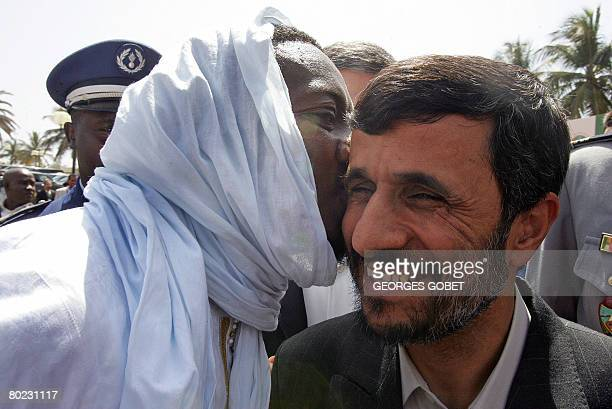 An unidentified person embraces Iranian President Mahmoud Ahmedinejad as Kings and heads of states attending the 11th Organisation of the Islamic...