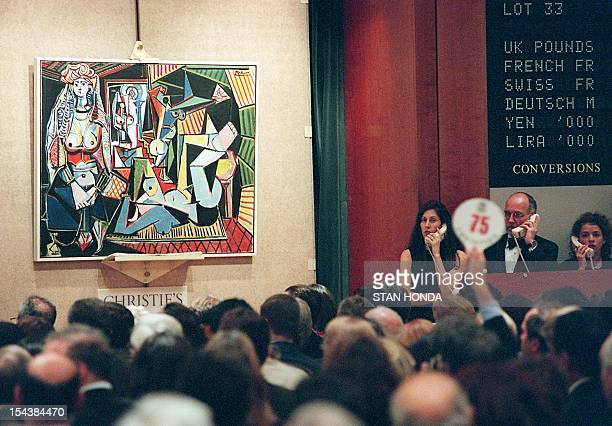 An unidentified person holding numbered paddle makes a bid on Pablo Picasso's painting 'Les femmes d'Alger' 10 November in New York at Christie's...
