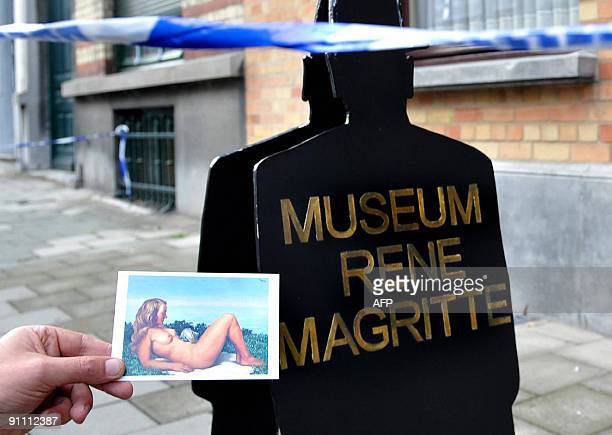 An unidentified person holds a postcard sized reproduction of Magritte's painting 'Olympia' in front of the former house of Belgian surrealist Rene...