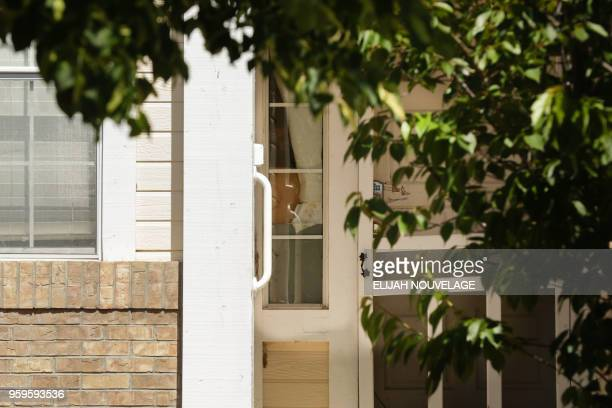 An unidentified person is seen peeking inside the home where 10 children were allegedly tortured and abused on May 17 in Fairfield California A...