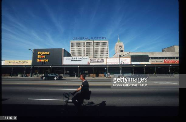 An unidentified person rides a bike near the General Motors headquarters June 29, 1998 in Flint, MI. The United Auto Workers Union strike has...