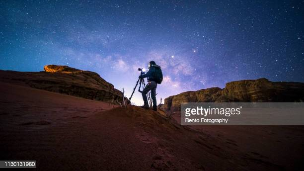 an unidentified photographer in wadirum desert under the milky way, jordan - jordan middle east stock pictures, royalty-free photos & images