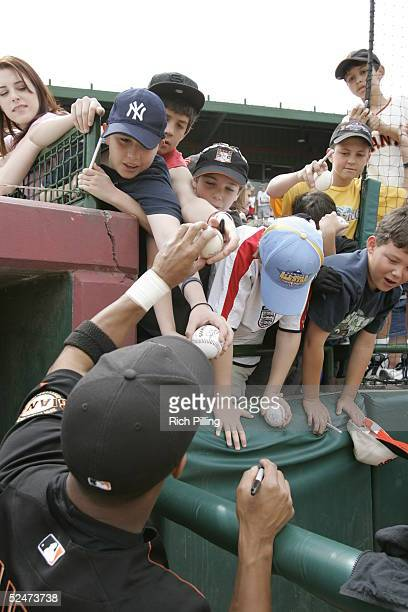 An unidentified player of the San Francisco Giants signs autographs before the Spring Training game against the Seattle Mariners at Scottsdale...