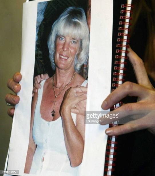 An unidentified police officer holds Tuesday December 13 a picture of motheroftwo Anne Curry who was snatched from her home at Dromore Co Down on...