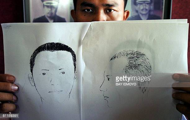 An unidentified police official displays sketches in Jakarta 11 August 2004 of suspects in the bombing of election commission office last July 26 A...