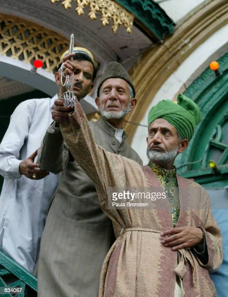 An unidentified priest is aided by other unidentified officials as they hold up relicts of the Sufi Saint Hazrat Gousul Azam Dastageer to the public...