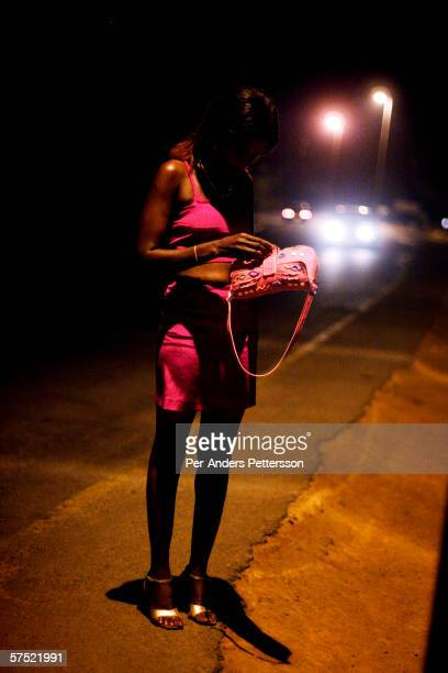 An unidentified prostitute stands along the highway at night on October 18 2005 in Lonzo outside Blantyre Malawi Hundreds of young women and girls...
