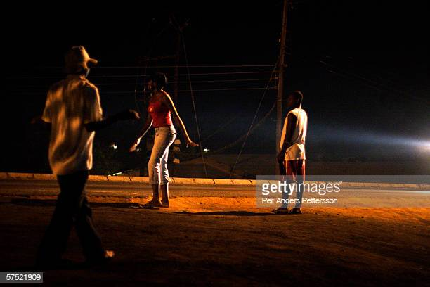 An unidentified prostitute walks along the highway at night on October 18 2005 in Lonzo outside Blantyre Malawi Hundreds of young women and girls...