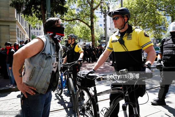 An unidentified protester clashes with a police officer during a demonstration between the left and right at Pioneer Courthouse Square on June 29...
