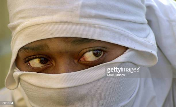 An unidentified protester peers out from a mask at the New Frienship Baptist Church during a rally for peace April 12 2001 in Cincinnati OH The city...