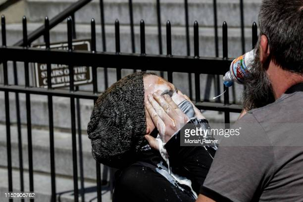 An unidentified protester relieves pepper spray with milk of magnesia after an attack during a demonstration between the left and right on June 29...