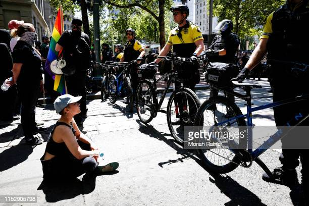 An unidentified protester sits to peacefully oppose to the police during a demonstration between the left and right at Pioneer Courthouse Square on...