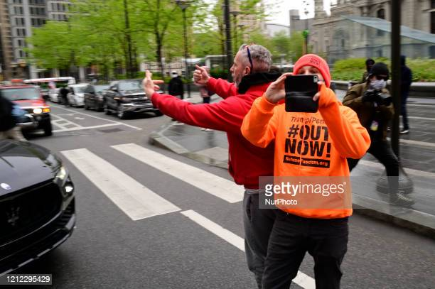 An unidentified protestor helps maneuver a vehicle past counter-protestors as a dozen vehicles participate in a anti-quarantine and reopen the...