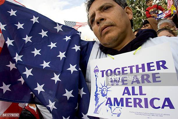 An unidentified protestor stands with thousands of people protesting immigration reform outside La Placita Church on April 10 2006 Crowds of people...