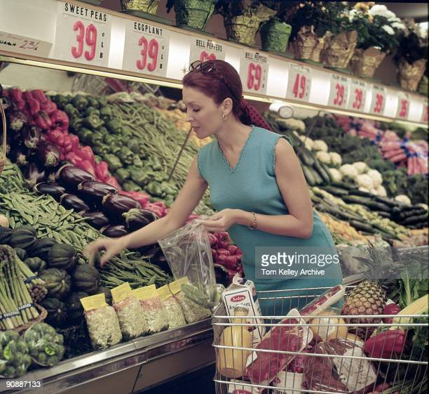 An unidentified redheaded model in a sleeveless blue sweater shops for peas in a Gelson's Super Market California 1970s