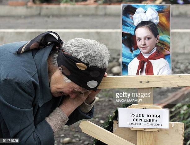 An unidentified relative of Yulia Rudik victim of the Beslan school siege mourn 13 October 2004 at the cemetery in the north Ossetian town This week...