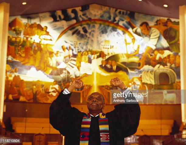 An unidentified religious leader raises his hands as he looks upwards during a church service Los Angeles California 1992 The wall behind him is...
