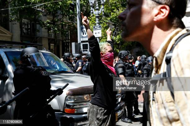 An unidentified Rose City Antifa member flicks off to the police during a demonstration between the left and right at Pioneer Courthouse Square on...