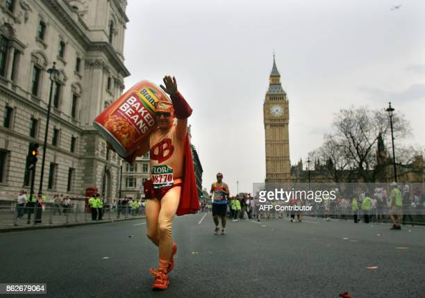 An unidentified runner dressed in a novelty costume runs with an oversized can of baked beans passes Big Ben as he makes his way towards the finish...