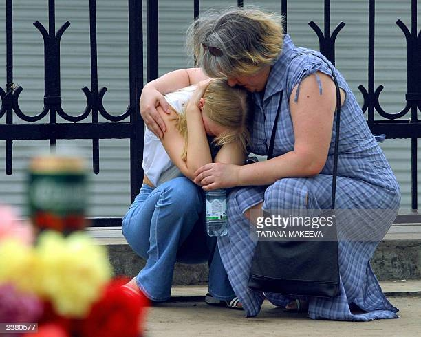 An unidentified Russian woman comforts a girl 06 July 2003 at the site in Moscow where two female suicide bombers blew themselves up at rock festival...