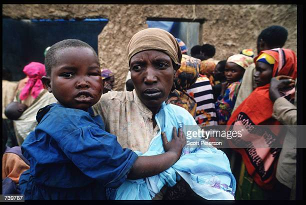 An unidentified Rwandan woman holds a child April 30 1994 as others file past her in Tanzania Two hundred fifty thousand refugees cross the border to...