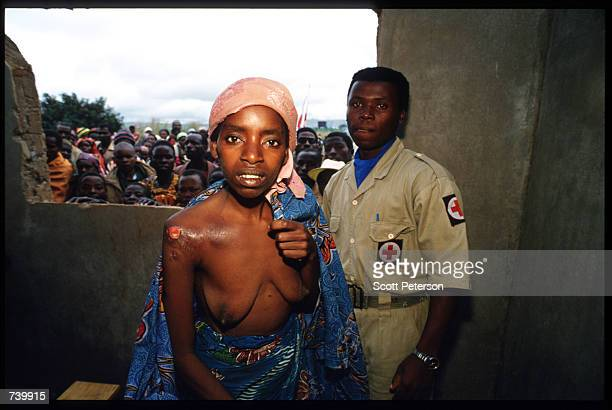 An unidentified Rwandan woman sits for a medical exam April 30 1994 as others look on in Tanzania Two hundred fifty thousand refugees cross the...