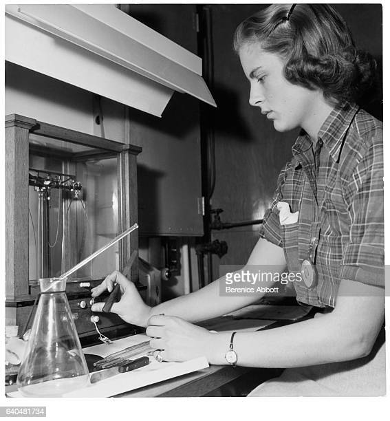 An unidentified scientist adjusts the dial of an unspecified apparatus as she performs an experiment at the Standard Oil laboratory New Jersey late...