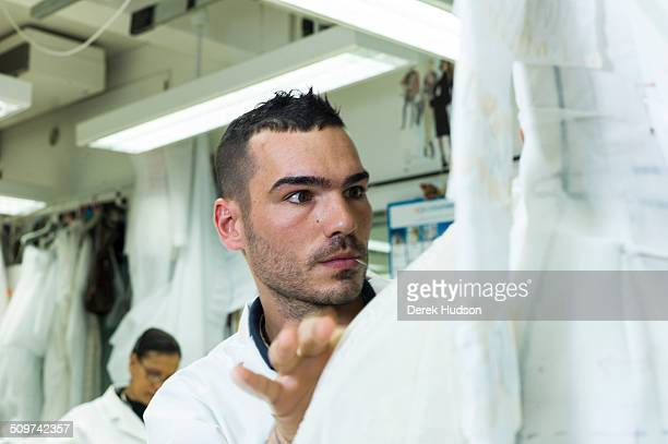 An unidentified seamster in the Dior atelier works on one of John Galliano's designs for his fashion show Paris France 2010