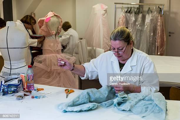An unidentified seamstress in the Dior atelier works on one of John Galliano's designs for his fashion show Paris France 2010