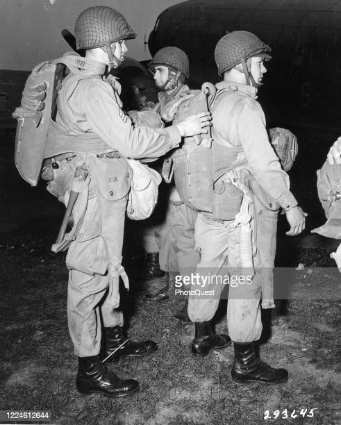 An unidentified section sergeant of paratroopers from Battery C 377th Field Artillery 101st Airborne Division inspects his men's parachutes before...