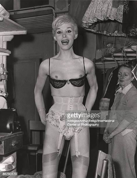 An unidentified showgirl in heavy stage makeup stands backstage in her brassiere with an assistant behind her 1940s or 1950s Photo by...