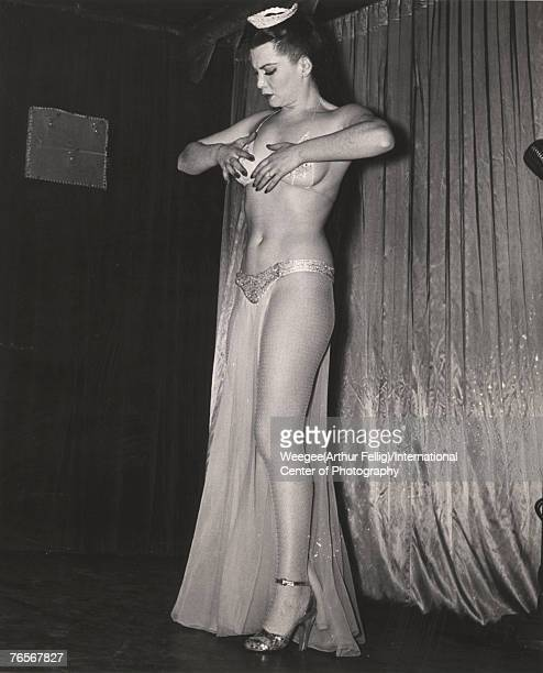 An unidentified showgirl performs on stage 1940s or 1950s She is dressed in a tiara transparent bikini partial skirt fishnet stockings and high heels...