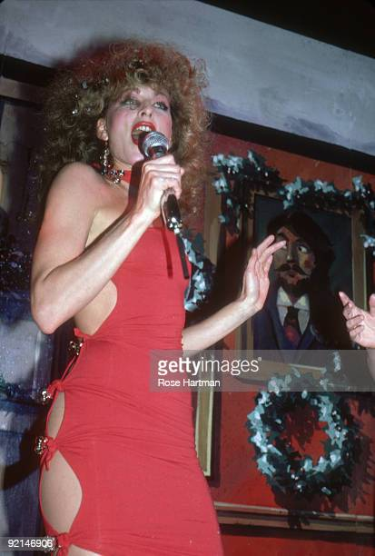 An unidentified singer in a red dress with cutaway panels and goldcolored metal buckles performs on stage during a Christmas party at the nightclub...