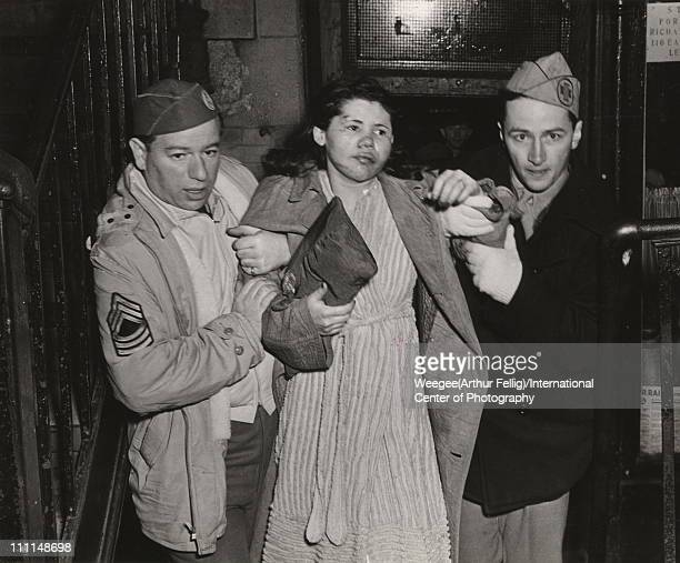 An unidentified soldier and air raid warden help Hortensia Nieves from a burning tenament New York New York April 20 1943 Nieves shows evidence of...